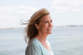 portrait of middle aged/senior woman with sea in the background