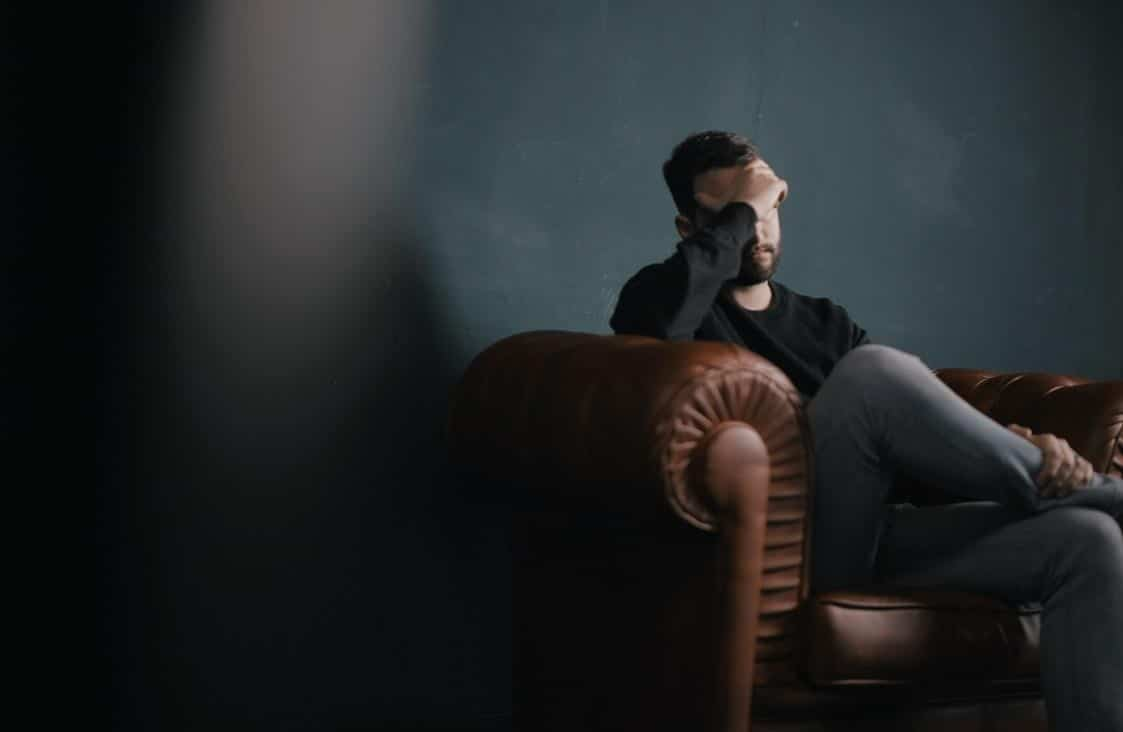 Depressed Man Sitting On Chair